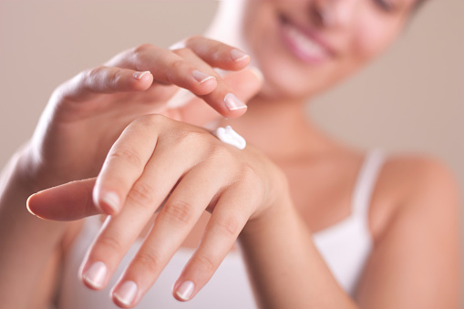 A woman applying hand lotion onto her hands 180956110