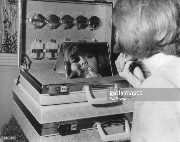 A woman applying her lipstick using the 'Golden Rhapsody' Revelation Duet Vanity Case which was on display at the 12th Annual Leathergoods Luggage...