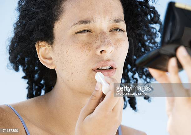 woman applying lip balm, holding compact - lip balm stock pictures, royalty-free photos & images