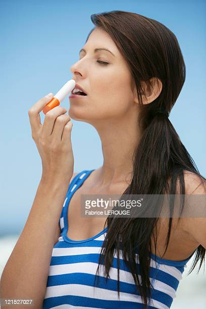 woman applying lip balm - lip balm stock pictures, royalty-free photos & images