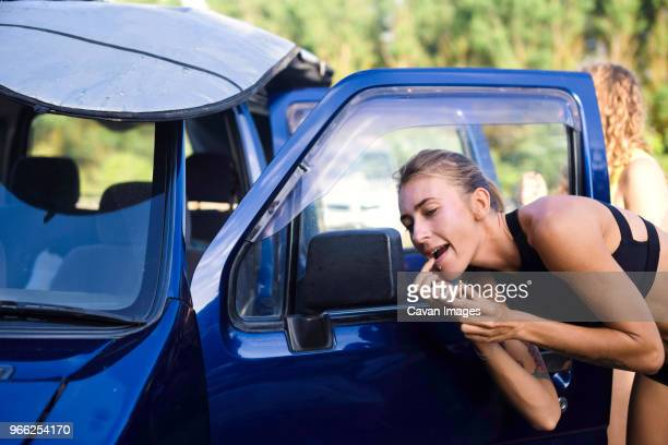 woman applying lip balm while looking in side-view mirror of car - lip balm stock pictures, royalty-free photos & images