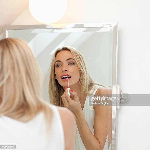 woman applying lip gloss in front of mirror