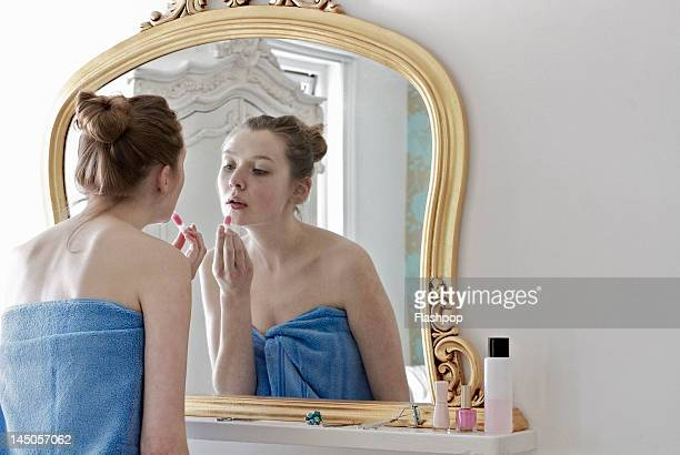 woman applying lip gloss - dressing table stock photos and pictures