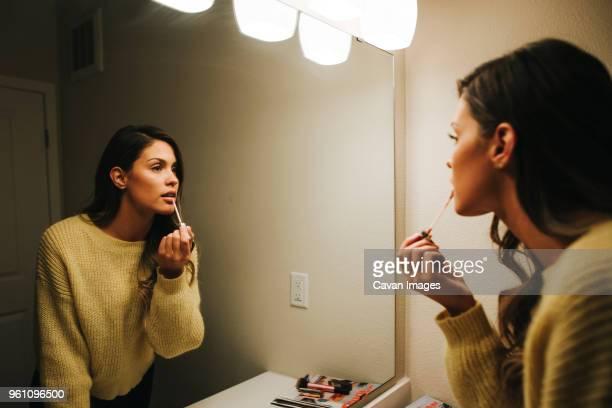 woman applying lip gloss reflecting on mirror at home - junge frau allein stock-fotos und bilder