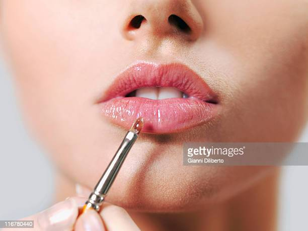 A woman applying lip gloss with a make-up brush, close-up of lips