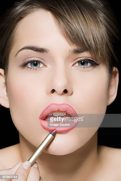 woman applying lip liner - lip liner stock photos and pictures