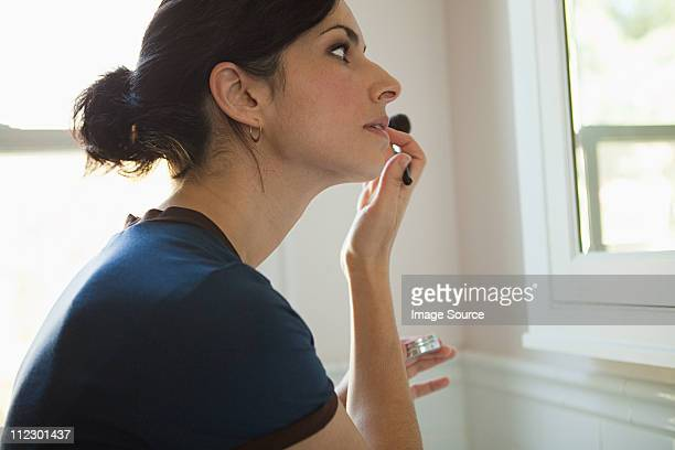 Woman applying lipgloss