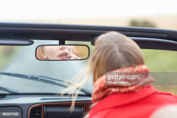Woman applying lipstick in car mirror.