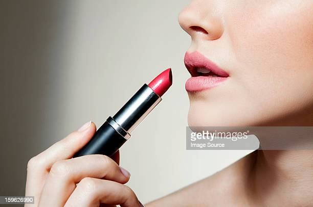 woman applying lipstick - lippenstift stock-fotos und bilder