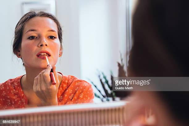 woman applying lipstick. - make up stockfoto's en -beelden