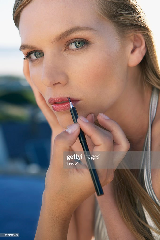 Woman applying lipstick to a beautiful woman : Stock Photo