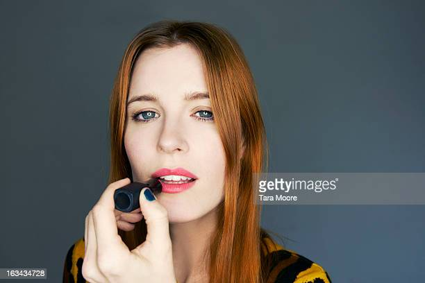 woman applying lipstick to lips in mirror - aplicando - fotografias e filmes do acervo