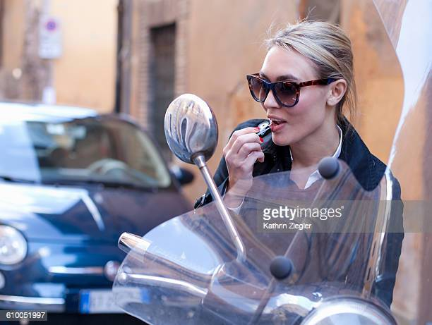 woman applying lipstick using side view mirror