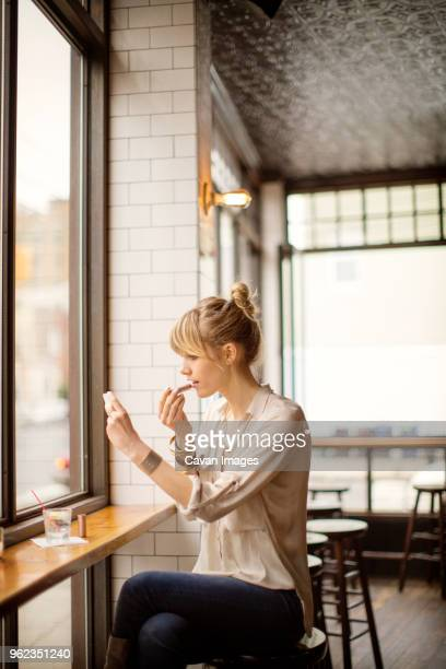 woman applying lipstick while sitting on stool in bar - powder compact stock pictures, royalty-free photos & images
