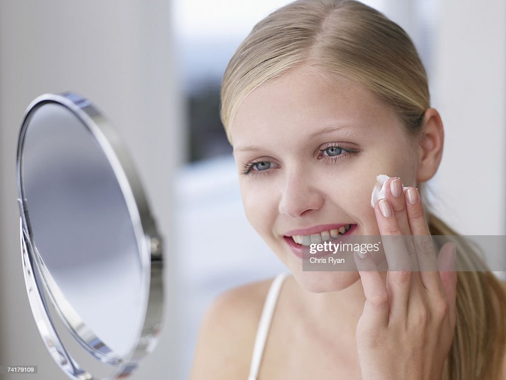 Woman applying lotion or cream to face in mirror : Stock Photo