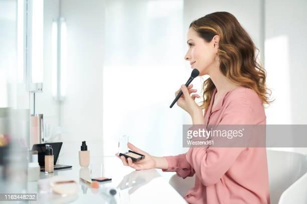 woman applying make up at home - make up stock-fotos und bilder