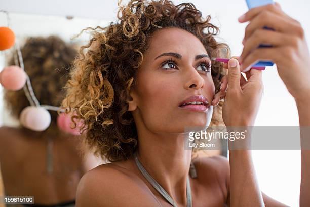 woman applying make up in mirror - 修眉 個照片及圖片檔