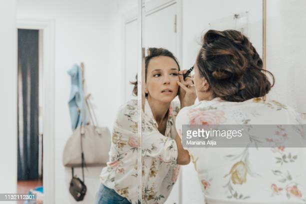 woman applying makeup before leaving - make up stockfoto's en -beelden