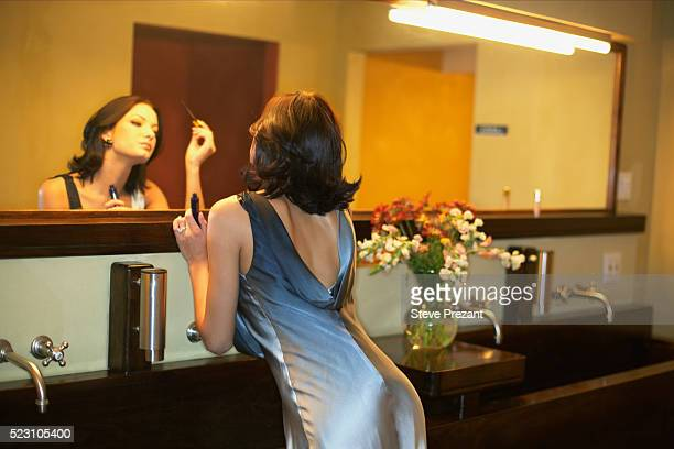 woman applying makeup in bathroom mirror - cocktail dress stock pictures, royalty-free photos & images
