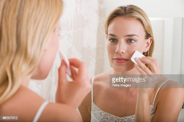 woman applying makeup in bathroom - padding stock photos and pictures
