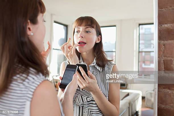 Woman applying make-up in front of mirror