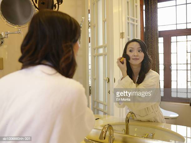 woman applying make-up in in bathroom, looking at mirror - vanity mirror stock photos and pictures