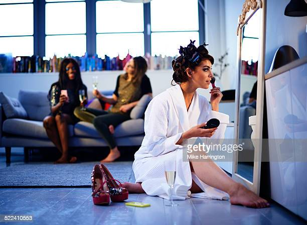 Woman applying make-up in mirror in lounge.