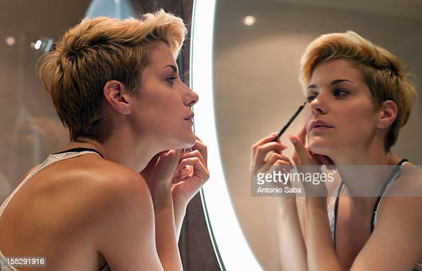 woman applying makeup in mirror - eyeliner stock pictures, royalty-free photos & images