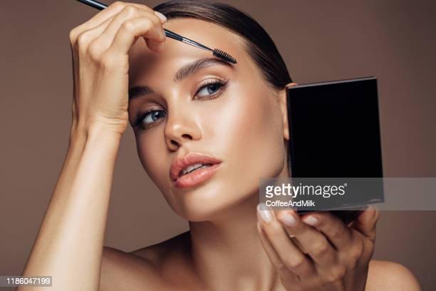 donna che applica il make-up - trucco per il viso foto e immagini stock