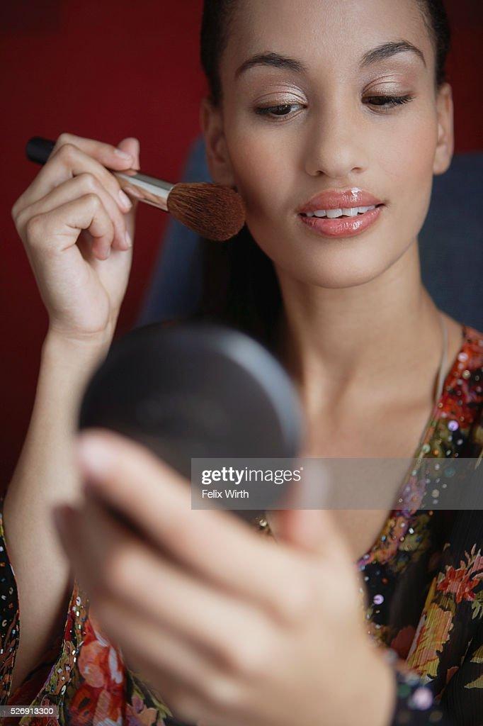 Woman applying make-up : Stock Photo