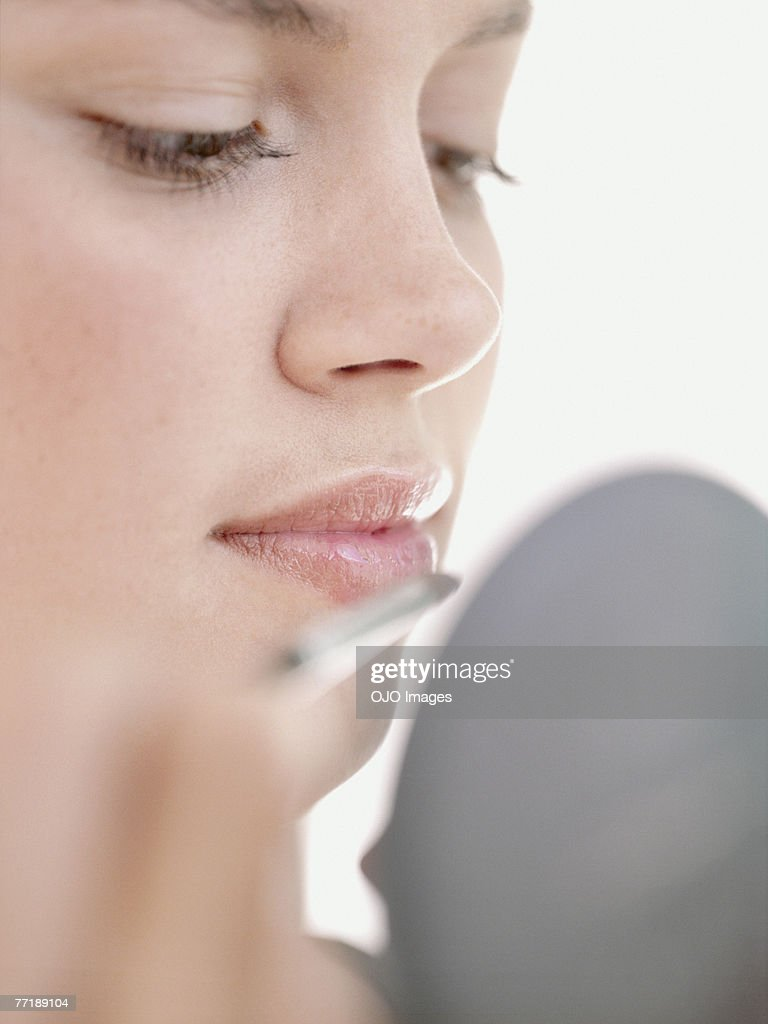 A woman applying make-up : Stock Photo
