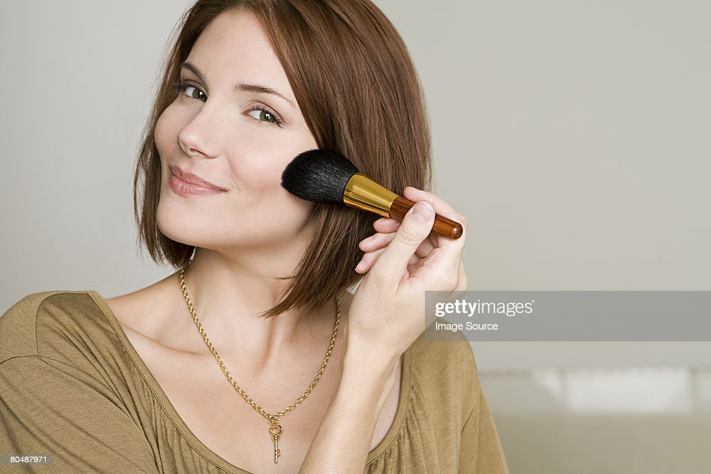 Woman applying makeup : Stock Photo