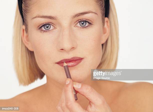 woman applying make-up - lip liner stock photos and pictures