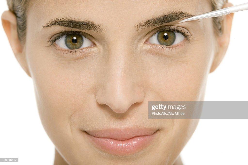 Woman applying make-up, smiling at camera : Stock Photo