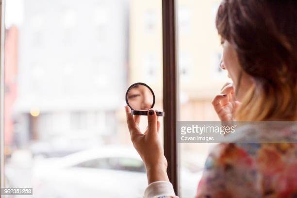 woman applying make-up while sitting in bar - powder compact stock pictures, royalty-free photos & images