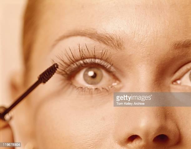 Woman applying mascara, close up