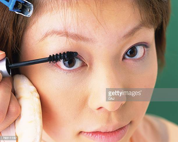 A Woman Applying Mascara, Front View, Looking at Camera, Differential Focus