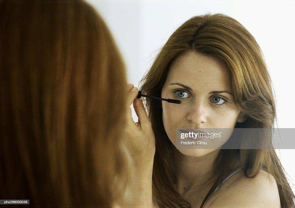 Woman applying mascara in mirror : Stockfoto