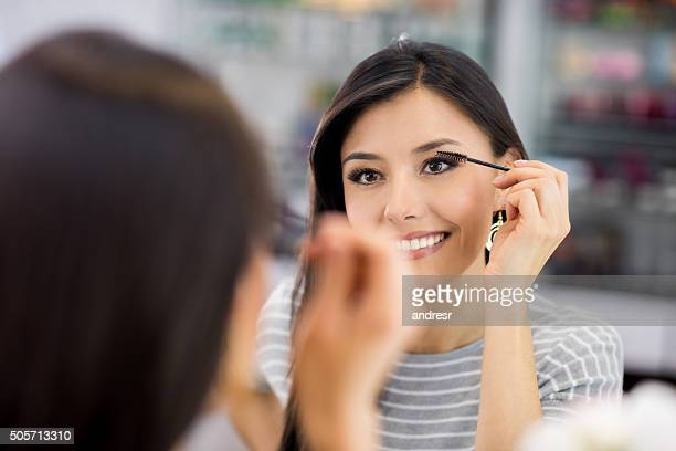 Woman applying mascara - makeup concepts