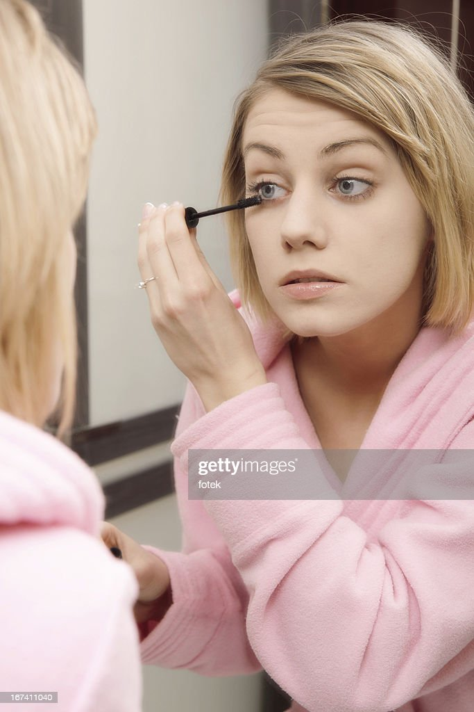 Woman applying mascara on eyelashes : Stock Photo