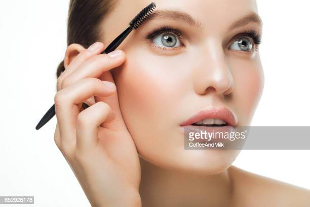 Woman applying mascara on eyelashes