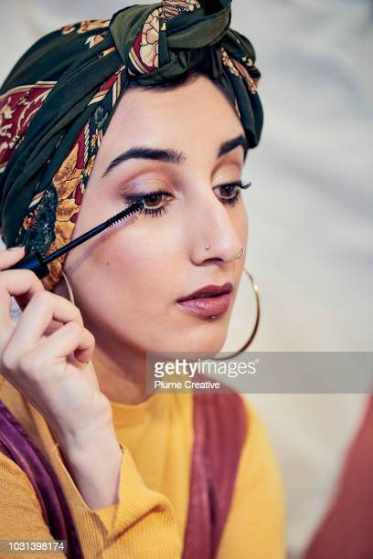 Woman applying mascara to lashes