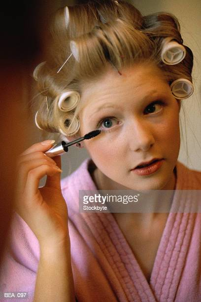 Woman applying mascara, wearing bathrobe, curlers in hair