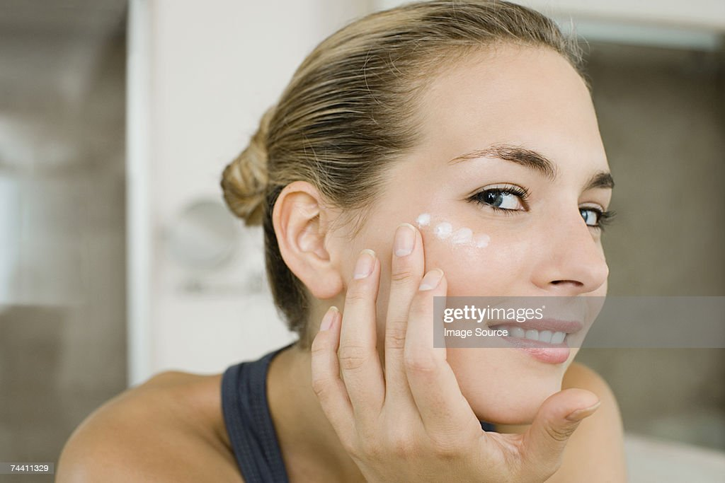 Woman applying moisturiser : Stock Photo