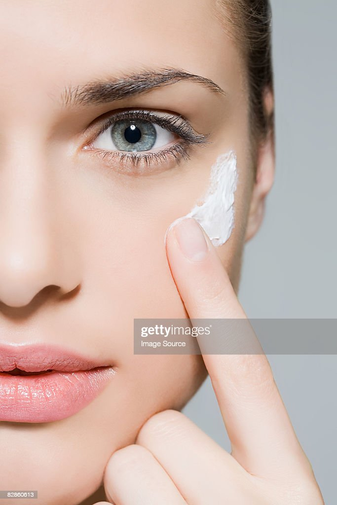 Woman applying moisturiser : Stock Photo