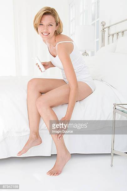 A woman applying moisturiser to her leg