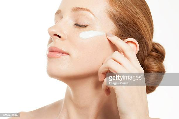 Woman applying moisturiser with eyes closed