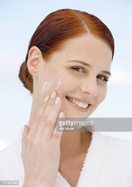 Woman applying moisturizer and wearing bathrobe