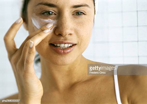 woman applying moisturizer beneath eye - moisturiser stock pictures, royalty-free photos & images