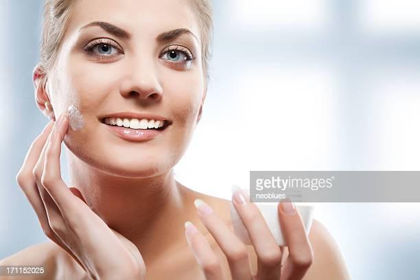 Frau Anwendung Feuchtigkeitscreme Creme auf Gesicht.